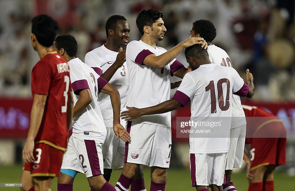 Qatar's Khalfan Ibrahim (R) celebrates with teammates after scoring a goal against Thailand during their friendly football match in the Qatari capital Doha on March 17, 2013.