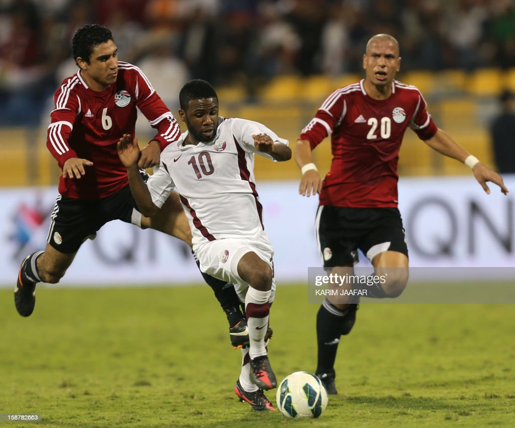 Qatar's Khalfan Ibrahim (C) challenges Egypt's Ramy Rabia (L) and Wael Gomaa (R) during their friendly football match in the Qatari capital Doha on December 28, 2012. Egypt won 2-0.