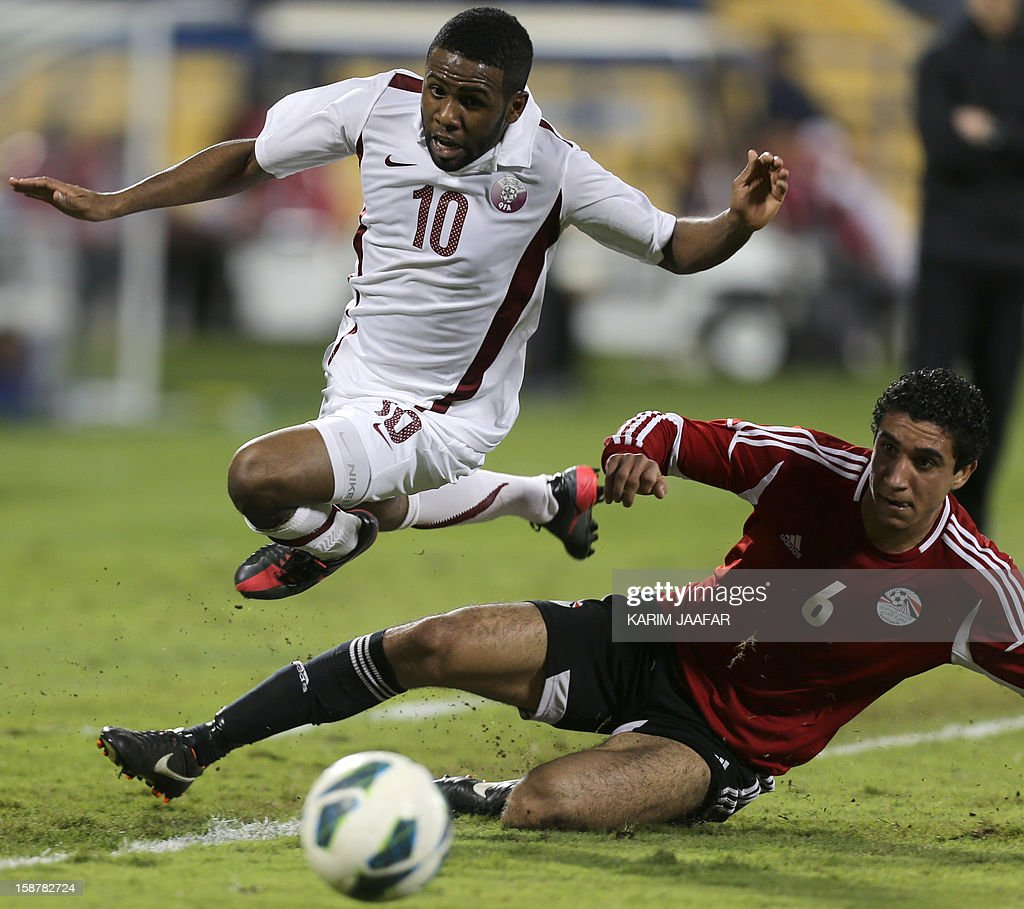 Qatar's Khalfan Ibrahim (L) challenges Egypt's Ramy Rabia during their friendly football match in the Qatari capital Doha on December 28, 2012. Egypt won 2-0.