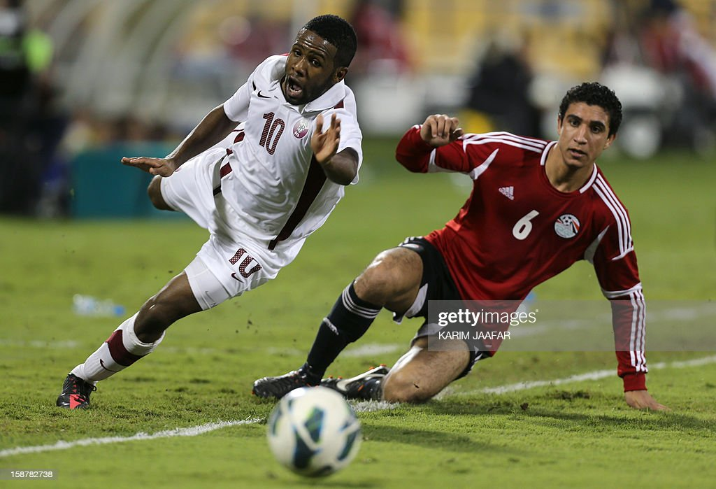 Qatar's Khalfan Ibrahim (L) challenges Egypt's Ramy Rabia during their friendly football match in the Qatari capital Doha on December 28, 2012. Egypt won 2-0. AFP PHOTO / AL-WATAN DOHA / KARIM JAAFAR == QATAR OUT ==
