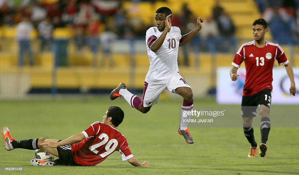 Qatar's Khalfan Ibrahim (C) vies with Egypt's Ahmed Shedid Qinawi (L) and Ahmed Magdi (R) during their friendly football match in the Qatari capital Doha on March 7, 2013. The match comes in the frame of the both national teams preparation for Asian and African qualification rounds for FIFA 2014 World Cup Finals in Brazil.