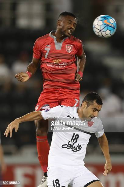 Qatar's Lekhwiya forward Ismail Mohamad and Iran's Persepolis FC defender Mohsen Nodehi jump to head the ball during the AFC Champions League...