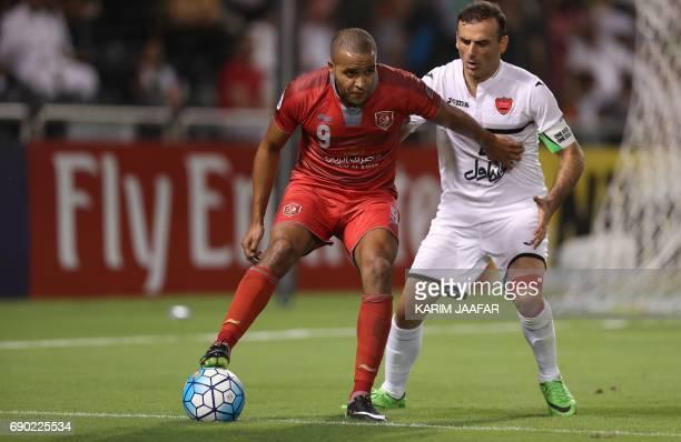Qatar's Lekhwiya SC forward Youssef ElArabi controls the ball as Iran's Persepolis FC defender and captain Seyed Jalal Hosseini defends during the...