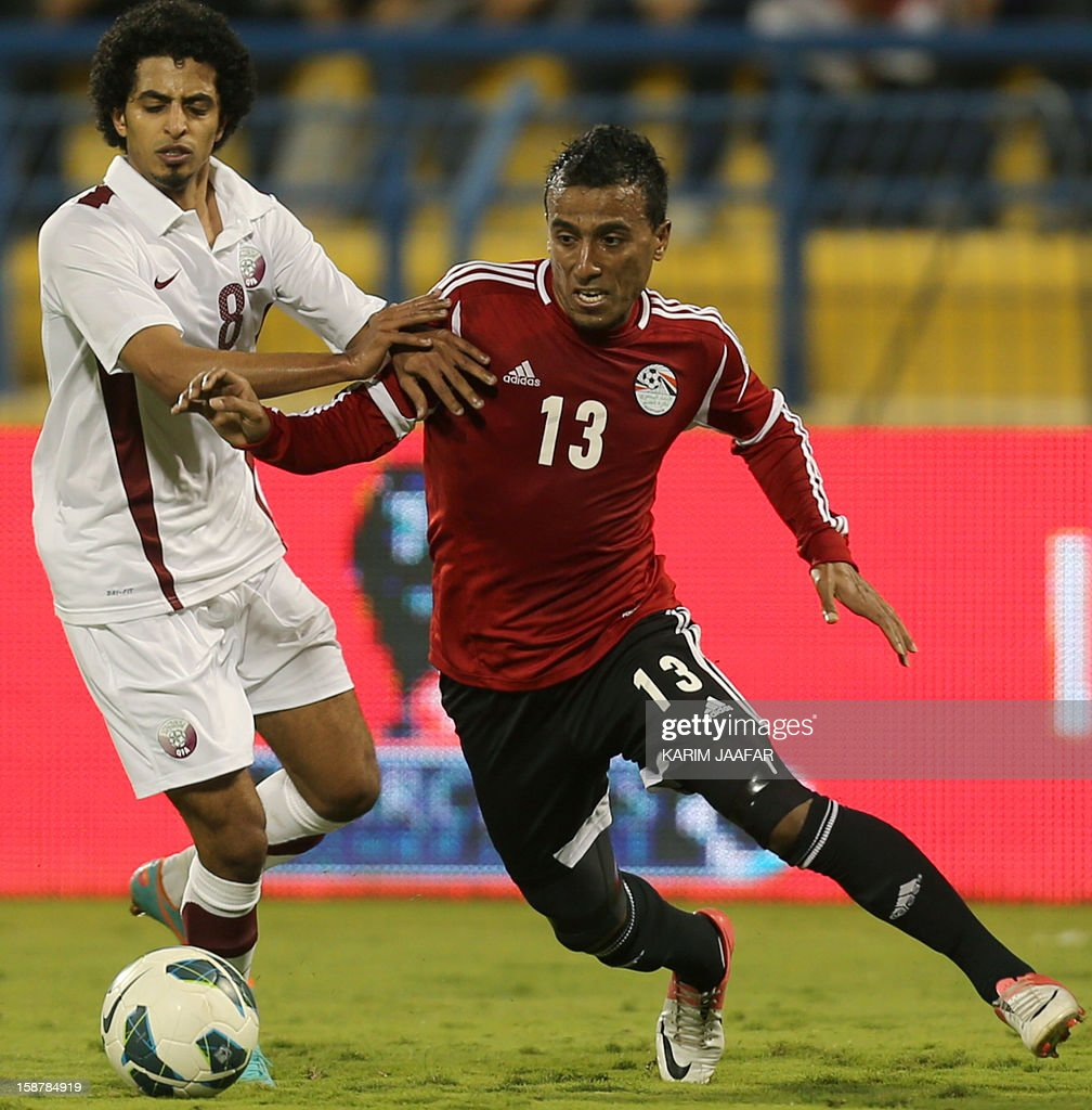 Qatar's Mesaad al-Hamad (L) fights for the ball with Egypt's Mohammed Abdel Shafi (R) during their friendly football match in the Qatari capital Doha on December 28, 2012. Egypt won 2-0. AFP PHOTO / AL-WATAN DOHA / KARIM JAAFAR == QATAR OUT ==