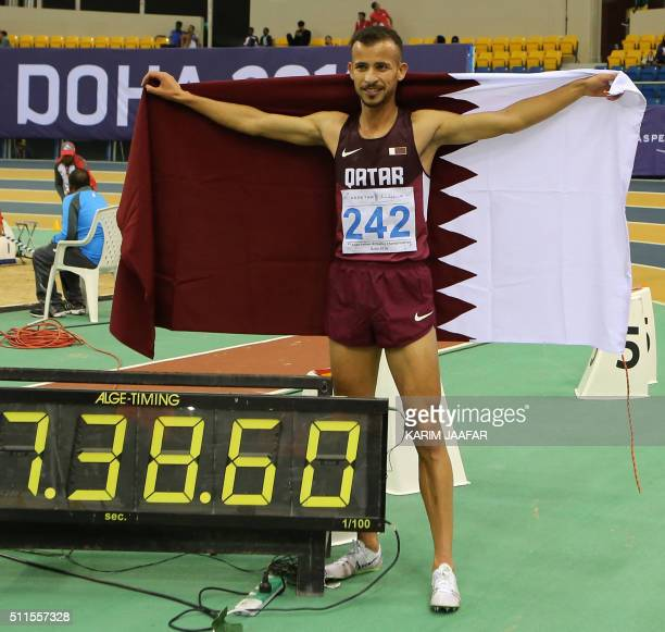 Qatar's Mohamad AlGarni celebrates holding his national flag after winning the 3000m event during the seventh Asian Indoor Athletics Championships at...