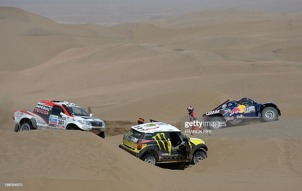 Qatar's Nasser Al-Attiyah (R) drives past as Mini's driver Nani Joan Roma (C) of Spain is assisted by Toyota's driver Giniel De Villiers of South Africa during the Stage 6 of the 2013 Dakar Rally between Arica and Calama, Chile, on January 10, 2013. The rally is taking place in Peru, Argentina and Chile from January 5 to 20.