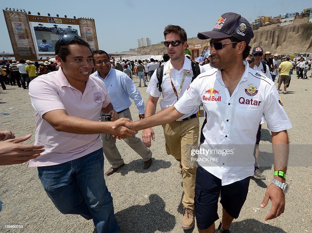 Qatar's Nasser Al-Attiyah (R) shakes hands with a supporter in Lima on January 4, 2013, ahead of the 2013 Dakar Rally which this year will thunder through Peru, Argentina and Chile from January 5 to 20. AFP PHOTO / FRANCK FIFE