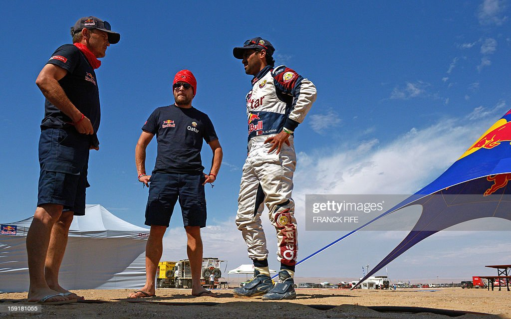 Qatar's Nasser Al-Attiyah (R) speaks with staff members in Chilean city of Arica after the 5th Stage Arequipa-Arica of the Dakar 2013 race, on January 9, 2013. The rally takes place in Peru, Argentina and Chile from January 5 to 20.