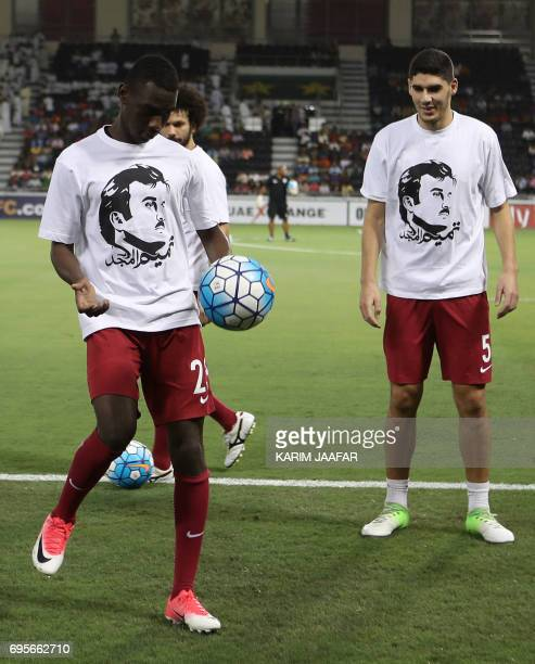 Qatar's national team players Karim Boudiaf and Ali Almoez wear tshirts bearing portraits of Emir Sheikh Tamim bin Hamad AlThani in support the...