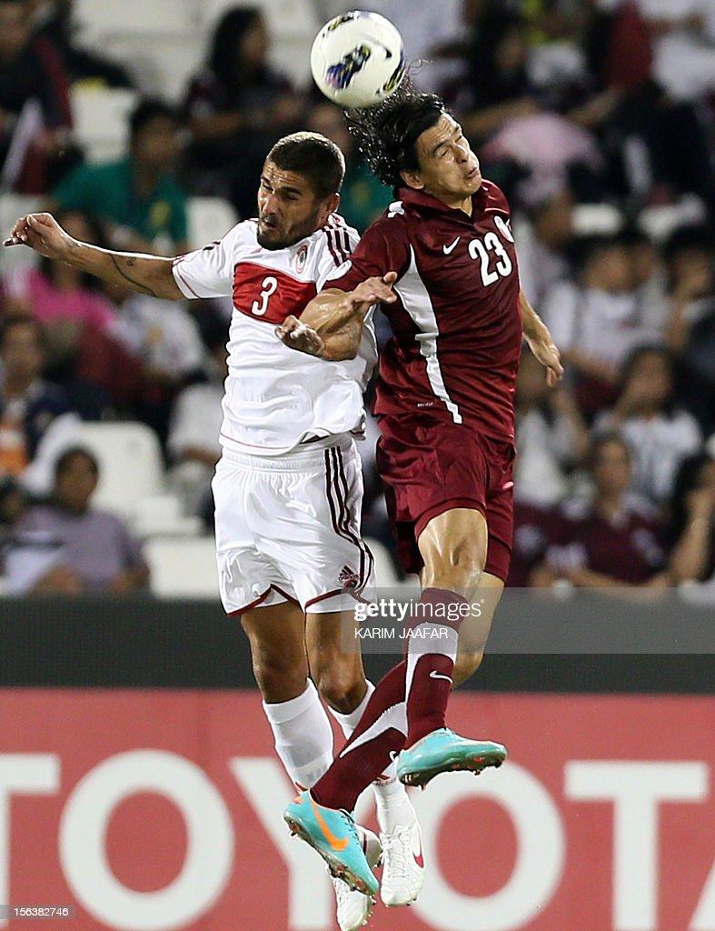 Qatar's Sebastian Soria and Lebanon's Yussef Mohammed jump for a header during their 2014 World Cup Asian zone group A qualifying football match in...