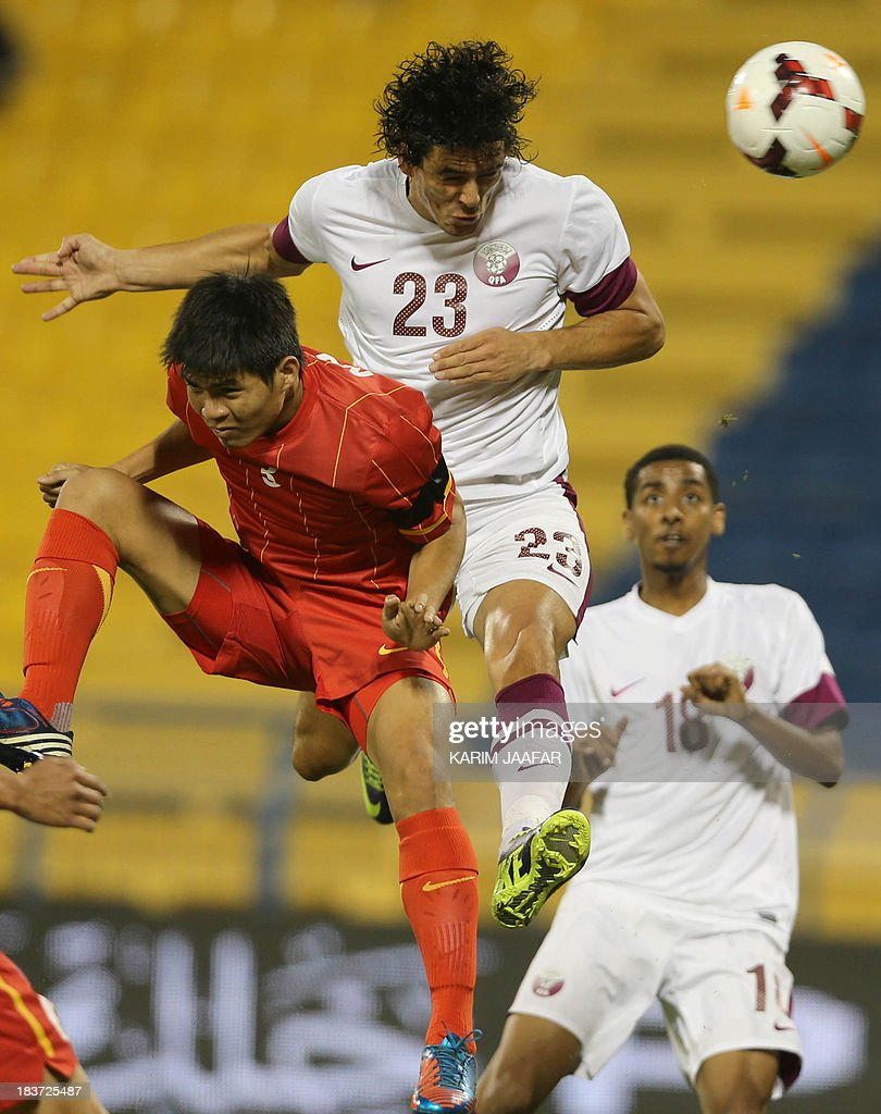 Qatar's Sebastian Soria challenges Nguyen Gia Tu of Vietnam for the ball as his teammate Mohammed elSayed watches on during their friendly football...