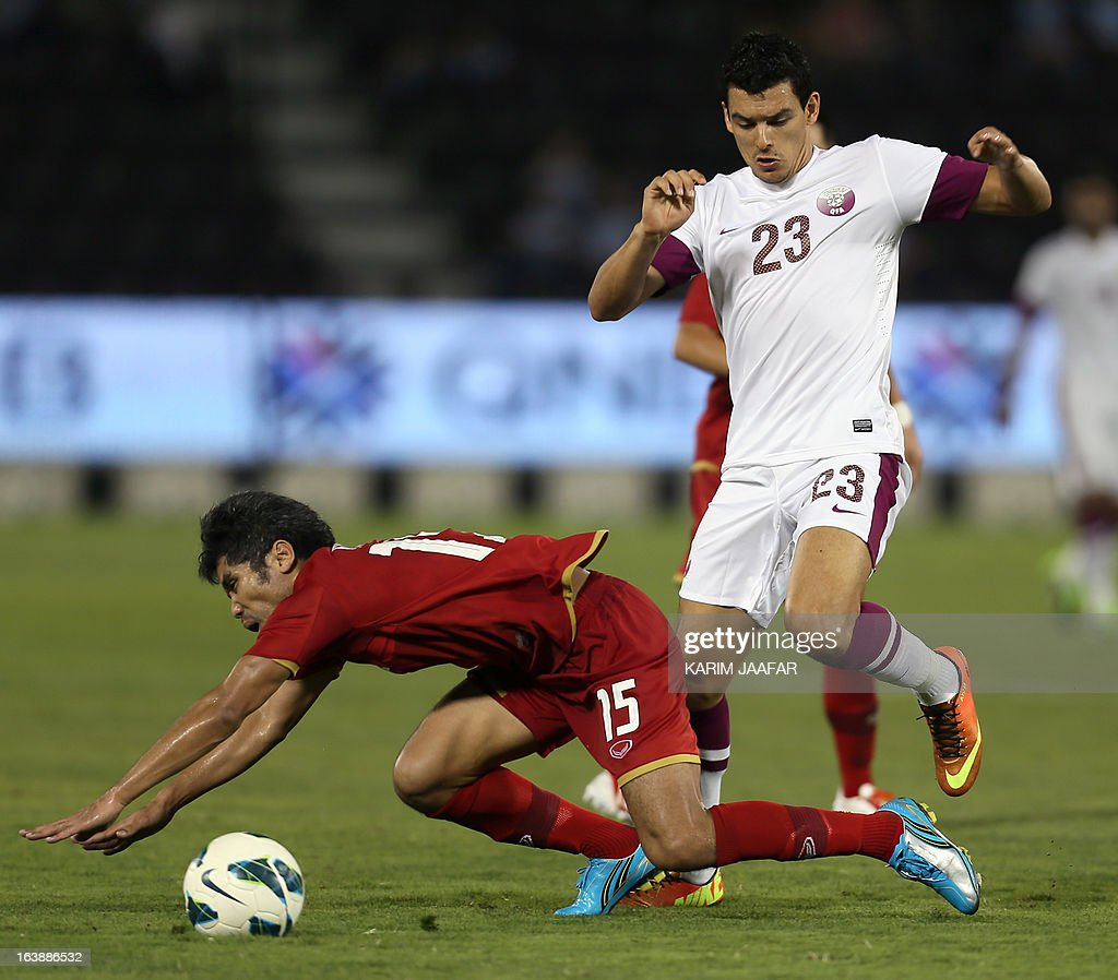 Qatar's Sebastian Soria (R) vies for the ball with Thailand's Surat Sukha during their friendly football match in the Qatari capital Doha on March 17, 2013.
