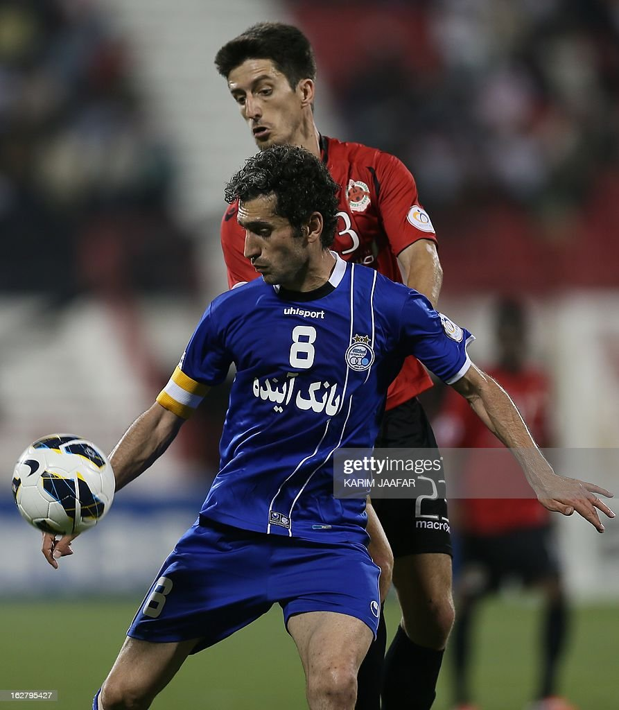 Qatar's Uruguayan midfielder Alvaro Fernandez (back) vies with Iran's Mojtaba Jabari during the AFC Champions League football match Iran's Esteghlal versus Qatar's al-Rayyan clubs in the Qatari capital Doha on February 27, 2013. AFP PHOTO / AL-WATAN DOHA / KARIM JAAFAR == QATAR OUT ==