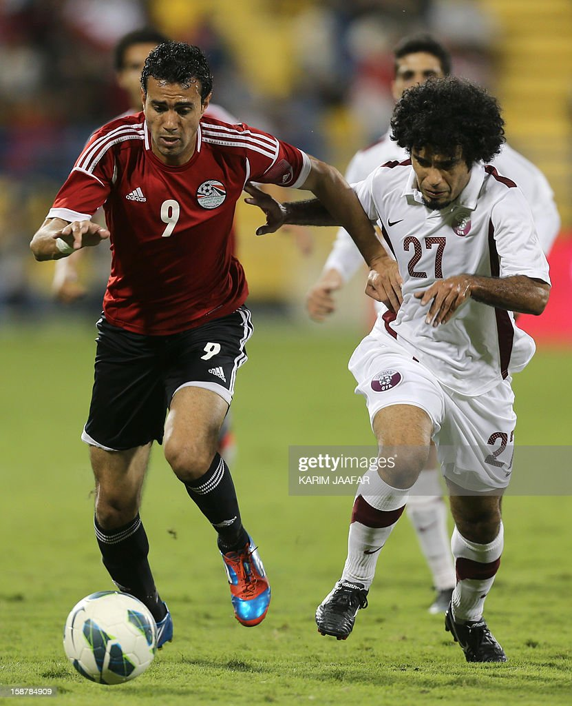 Qatar's Yunes Ali (R) challenges Egypt's Ahmed Mekki during their friendly football match in the Qatari capital Doha on December 28, 2012. AFP PHOTO / AL-WATAN DOHA / KARIM JAAFAR == QATAR OUT ==