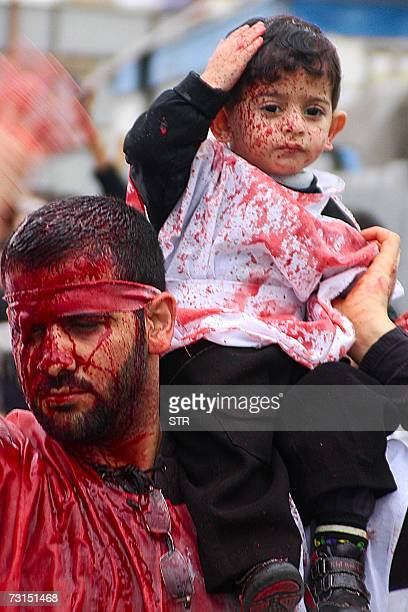 A Saudi Muslim Shiite man covered in his blood carries his son on his shoulder during a ceremony to mark Ashura in Qatif in Saudi Arabia's oilrich...