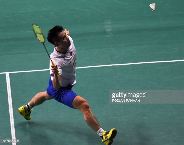 Qiao Bin of China returns a shot against Sai Praneeth of India during the men's singles round two qualifying at the Singapore Open badminton...