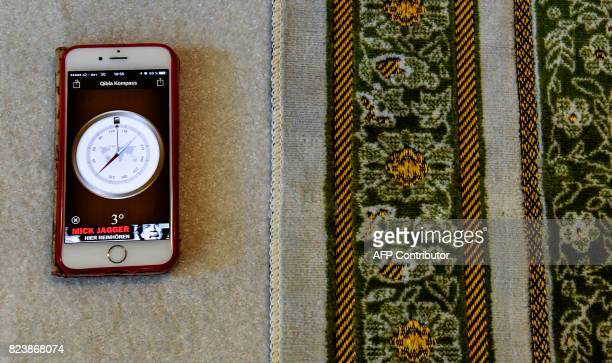 A 'Qibla Compass' app on a smartphone shows the prayer direction next to a prayer mat prior to Friday prayers at the Ibn RushdGoethemosque in Berlin...