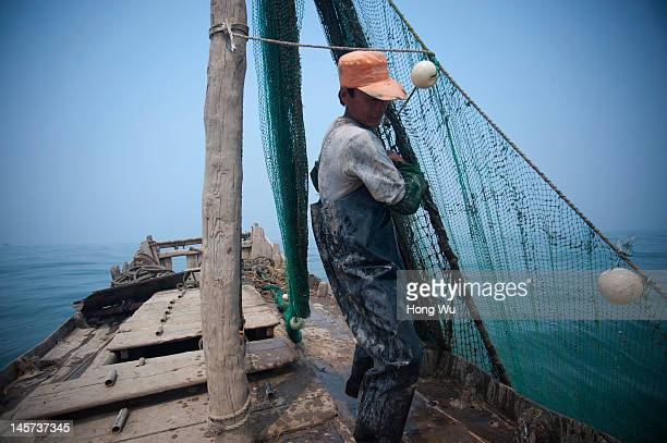 Qu Lin a 45yearold Chinese fisherman uses fishing net to fish on his 8 meters long fishing boat lonely as he no money to employ helper on May 28 2012...