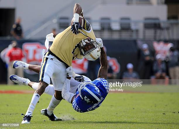 Qua Search of the Georgia Tech Yellow Jackets is tackled by Mike Edwards of the Kentucky Wildcats during the first half of the game at EverBank Field...
