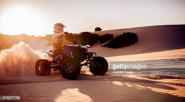 Quad bike racer in protective gear driving on sand dunes