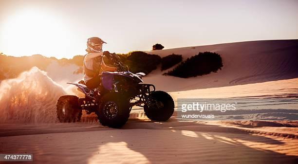 Quad bike racer in schützende Kleidung fahren auf sand dunes