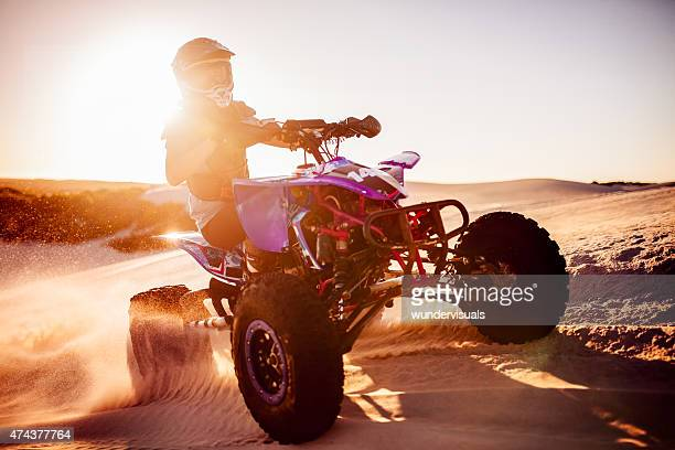Quad biker in desert race with sun flare behind