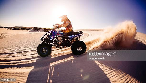 Quad biker kicking up sand while racing on sand dunes