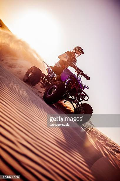 Quad biker on a sand dune in a desert race