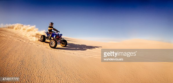 Quad biker racing downhill in a desert race