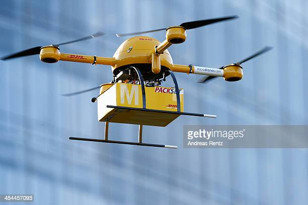 A quadcopter drone arrives with a small delivery at Deutsche Post headquarters on December 9 2013 in Bonn Germany Deutsche Post is testing deliveries...