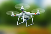 Creative abstract 3D render illustration of professional remote controlled wireless RC quadcopter drone with 4K video and photo camera for aerial photography flying in the air outdoors with selective