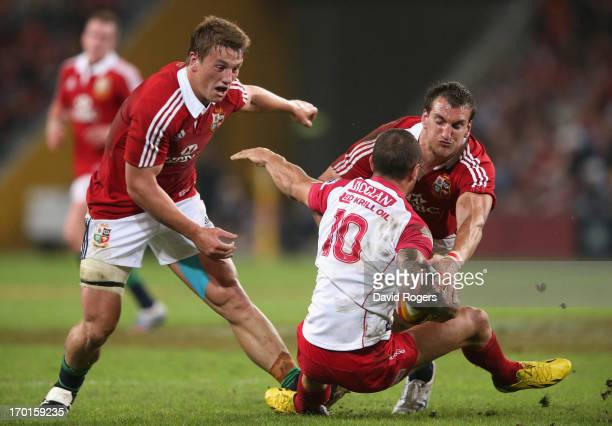 Quade Cooper of Queensland Reds is tackled by Sam Warburton and Jonathan Davies during the match between the Queensland Reds and the British Irish...