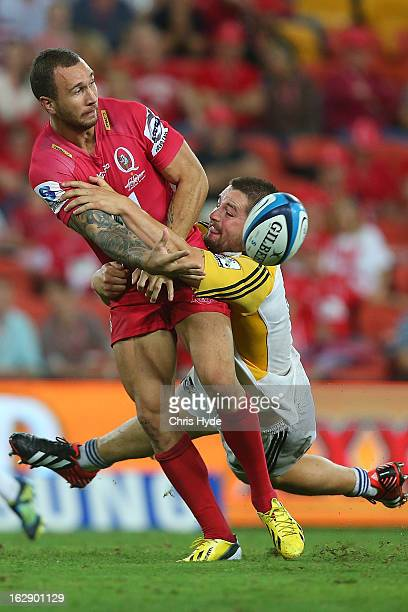 Quade Cooper of the Reds is tackled by Dane Coles of the Hurricanes during the round three Super Rugby match between the Reds and the Hurricanes at...
