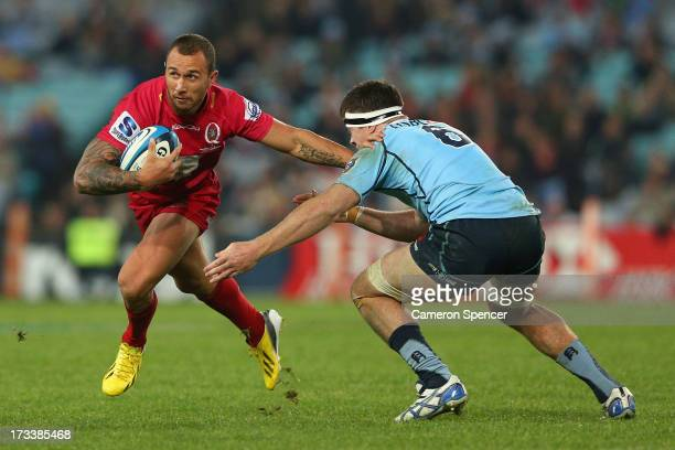 Quade Cooper of the Reds runs the ball during the round 20 Super Rugby match between the Waratahs and the Reds at ANZ Stadium on July 13 2013 in...