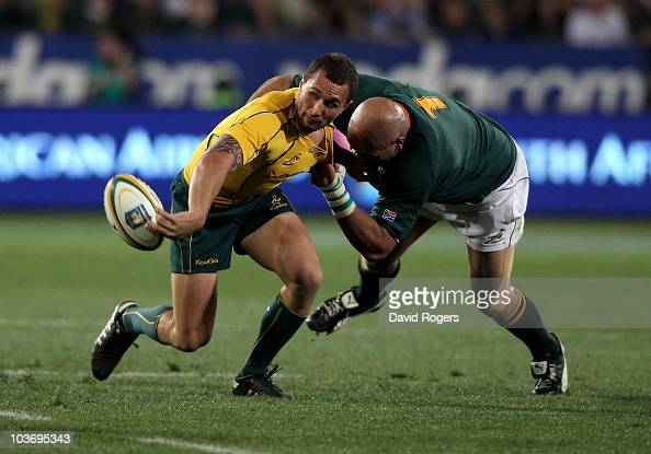 Quade Cooper of the Wallabies off loads the ball as Gurthro Steenkamp tackles during the 2010 TriNations match between the South African Springboks...