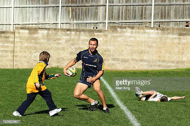 Quade Cooper plays with young fans during an Australian Wallabies training session at Coogee Oval on July 15 2010 in Sydney Australia