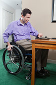 Quadriplegic man in wheelchair with spinal cord injury using his electronic tablet for e-mail