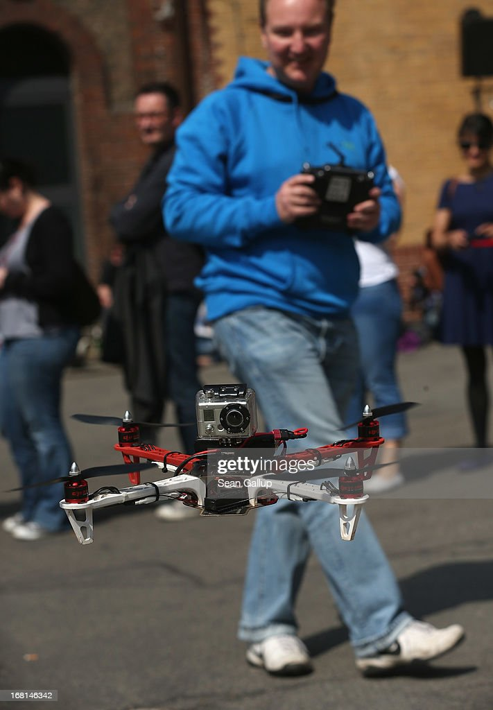 A quadrocopter drone flown remotely by a participant and equipped with a video camera flies past other participants waiting in line for regsitration on the first day of the re:publica 2013 conferences on May 6, 2013 in Berlin, Germany. Re:publica, a three-day-event, brings together bloggers and digitial media professionals for a series of conferences on affecting social, political and economic change through the Internet.