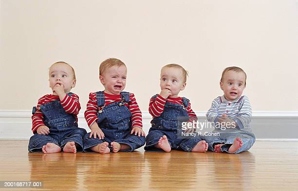 Quadruplet babies (9-12 months) sitting side by side on hardwood floor