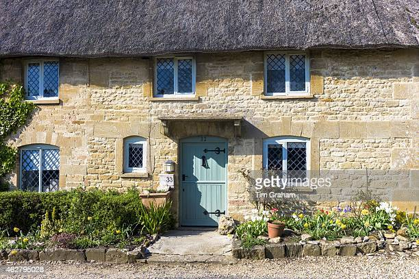 Quaint thatched cottage with traditional thatching and leaded light windows at Taynton in The Cotswolds Oxfordshire UK