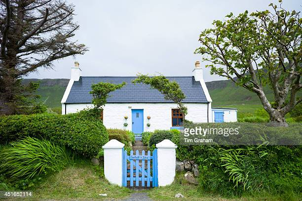 Quaint traditional highland cottage in patriotic blue and white colours to match Scottish flag near Linicro in the Highlands of Scotland