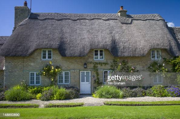 Quaint traditional thatched cottage in Minster Lovell in The Cotswolds Oxfordshire UK