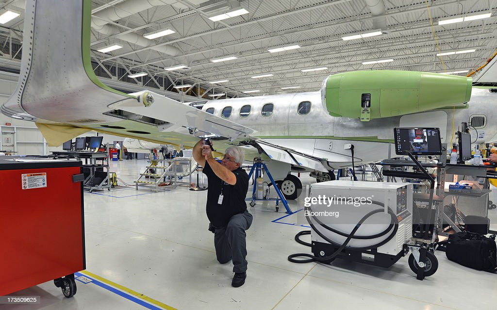 Quality assurance inspector Mike Pettis inspects a flap assembly on an Embraer SA Phenom 300 Light business jet at the company's executive jet manufacturing facility in Melbourne, Florida, U.S., on Monday, July 15, 2013. Embraer SA, the world's largest manufacturer of commercial jets up to 120 seats, delivered 22 jets to the commercial aviation market and 29 to the executive aviation market, for a total of 51 aircraft in the second quarter of 2013, according to a company press release. Photographer: Mark Elias/Bloomberg via Getty Images