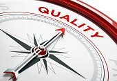 Arrow of a compass is pointing quality text on the compass. Arrow, quality text and the frame of compass are red in color. Horizontal composition qith copy space. Quality  concept.