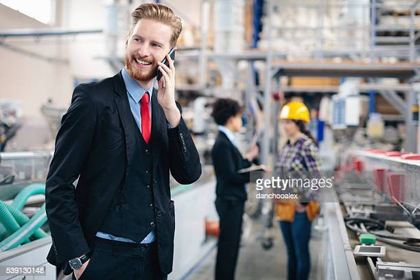 Quality inspector in a factory talking on the cell phone