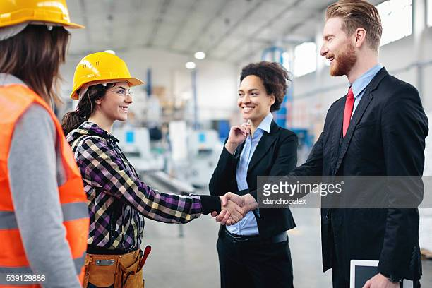 Quality inspectors shaking hands with workers
