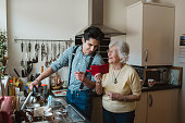 Senior woman is showing something to her grandson on her smart phone while he fills the kettle at the sink in her home. They are both laughing.