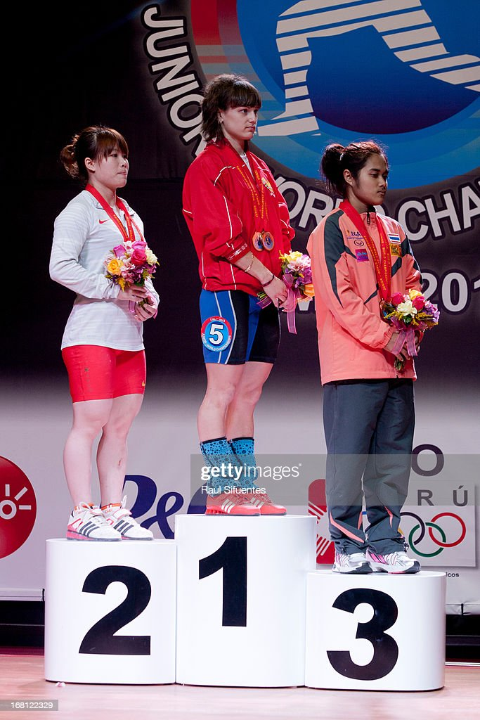 Quan Liu of China A (#L), Alena Chychkan of Belarus A (#C) and Sopita Tanasan of Thailand A (#R) stand on the podium of Total Women's 53kg during day two of the 2013 Junior Weightlifting World Championship at Maria Angola Convention Center on April 05, 2013 in Lima, Peru.