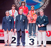 Quan Liu of China A Alena Chychkan of Belarus A and Sopita Tanasan of Thailand A stand on the podium of Total Women's 53kg with officials of IWF...