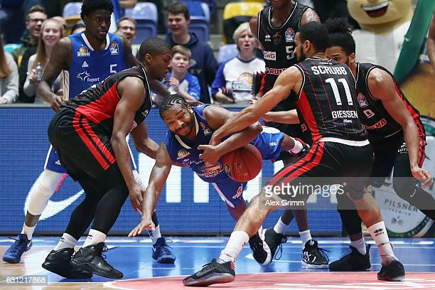 Quantez Robertson of Frankfurt is challenged by Cameron Wells and Thomas Scrubb of Giessen during the easyCredit BBL match between Fraport Skyliners...